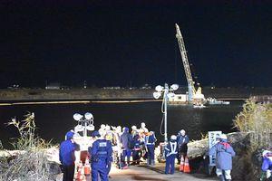 小型ボートが転覆し、川に投げ出された作業員を捜索する消防署員ら=8日午後5時半ごろ、つがる市稲垣町の岩木川