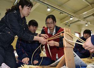 同校卒業生の村井さん(右から2人目)らに教わりながら、きみがら草履作りに挑戦する三農生たち