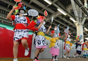 ハネト姿で跳びはねながら出発する新幹線を見送る青森西高の生徒たち=1日午前、新青森駅