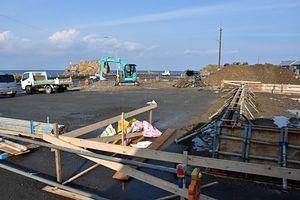 深浦町が整備する駐車場の一角にコンビニが出店する国道101号沿いの予定地。左奥は日本海と景勝地「大岩」