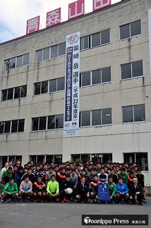 垂れ幕の前で柴崎選手を応援する青森山田高校のサッカー部員ら