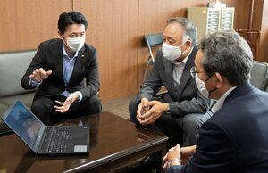 吉田教育長(中)らに動画の説明をする福井本部長(左)