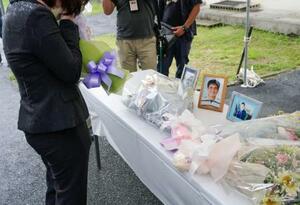 男子学生が自殺した現場に献花する遺族(左)=17日午後、山口県周防大島町