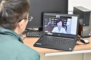 ビデオ会議ソフト「Zoom」を活用し、患者(左)を遠隔診療する東京女子医大・唐澤教授=9日、青森市の青森新都市病院