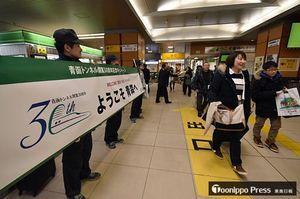 横断幕を掲げ新幹線利用客を出迎えるJR社員=10日午前、新青森駅