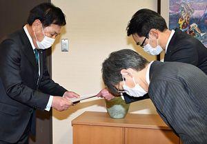 小早川社長からの書簡を越善村長(左)に手渡す宗常務(右奥)
