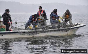 底引き網を小川原湖から引き揚げる米軍と海自の隊員ら=5日午前9時36分