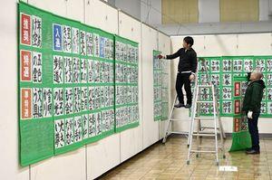 東奥児童書道展の入賞作品を展示するスタッフ