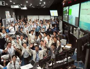 管制室でカメラに向かってVサインなどをして喜ぶ、はやぶさ2の運用チーム=11日午前10時50分ごろ、相模原市(JAXA提供)