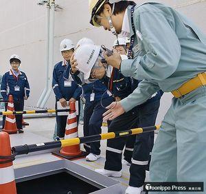 原燃社員(右)の説明を受けながら配管ピットの内部を確認する規制委の田中委員長代理(右から2人目)=7日午後、六ケ所村
