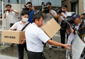 久保木愛弓容疑者の自宅アパートを家宅捜索し、押収品を運び出す捜査員ら=12日午後2時44分、横浜市鶴見区