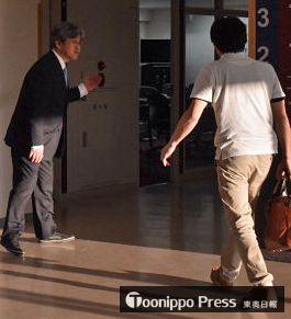 事故を受けた臨時集会の会場に向かう保護者(右)=22日午後6時ごろ、八戸市の八戸学院光星高校