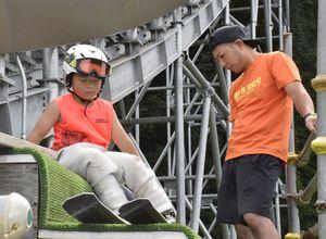 スキージャンプの練習に打ち込む原田君(左)。右は父の幹大さん=秋田県の花輪スキー場