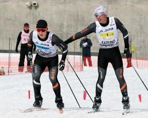 男子40キロリレーで優勝した飯山。アンカー高橋(左)にタッチする小林=花輪スキー場