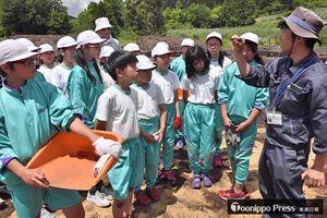 剣吉小児童を前に、発掘体験での出土品の説明をする布施総括主査(右)