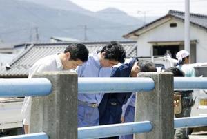 愛媛県西予市野村町の被災現場で黙とうする安倍首相(左から2人目)ら。左端は愛媛県の中村時広知事=13日午前11時40分ごろ(代表撮影)