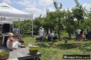 シードル工房の前で開かれた音楽イベント。高橋さんは「リンゴ園に市民が気軽に入れるようにしたい」と夢を語る=6月21日、市りんご公園