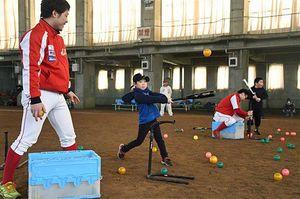 弘前アレッズの選手(左)からアドバイスを受け、ティーバッティングを体験する子どもたち
