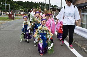 笑顔で横浜町内の道を練り歩く稚児ら=16日