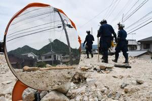 土砂に埋まったカーブミラーの横を歩き捜索に向かう警察官=11日午後0時45分、広島県呉市天応地区