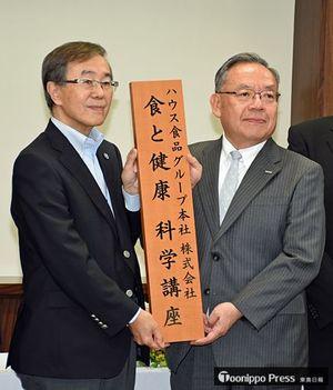 共同研究講座のプレートを掲げる田口取締役(右)と佐藤学長