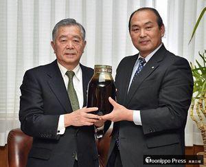 田子町に寄贈されたニンニクのしょう油漬けを持つ山本町長(右)と杉本みち銀会長
