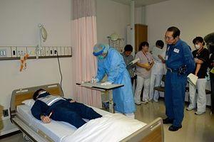 訓練で感染の可能性がある患者を診察する医師