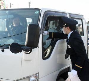 踏切を横断する車の運転手に安全運転を呼び掛けるJR新青森駅員=6日午前7時ごろ、青森市の石江踏切