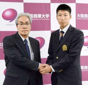 中日の米村明チーフスカウト(左)と握手する大商大の橋本侑樹投手=21日、大阪府東大阪市