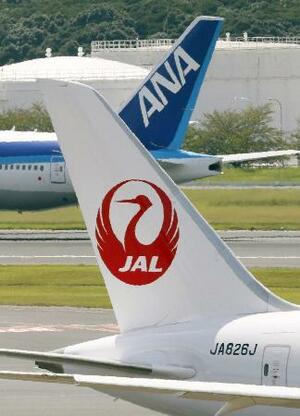 成田空港ですれ違う日航機(手前)と全日空機の尾翼