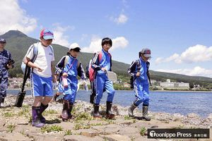 芦崎を散策した児童たち。背後には釜臥山と児童が通う大湊小学校の校舎(写真右奥)が見える