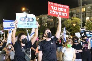 17日、イスラエルのテルアビブで行われたネタニヤフ首相の退陣を求めるデモで、プラカードを掲げる参加者ら(共同)