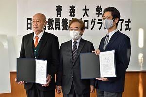 青森大の「日本語教員養成プログラム」の修了証書を受け取り、金井学長(中)と記念写真に納まる中野渡さん(左)、小野さん