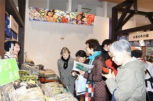 リニューアルオープンした旬味市で、訪れた多くの客が青森県の味覚や工芸品を品定めした。上部奥には北村さんが制作したねぶた型照明が設置されている=5日、JR新青森駅