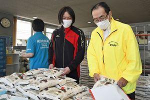 アップルマラソン参加者に贈る県産米を袋詰めする猪股実行委員長(右)ら=27日、弘前市の克雪トレーニングセンター