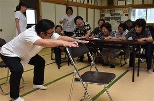 小野院長(手前)から健康づくりの体操を教わる地域住民。病院スタッフが町職員と一緒に地域に赴き、高齢者の健康維持活動を一体的に進めている=8月21日、七戸町の二ツ森地区コミュニティセンター