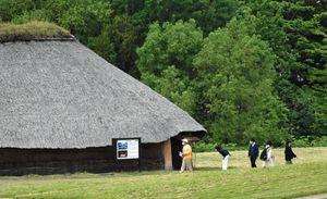 三内丸山遺跡を歩く見学者たち。新型コロナの影響で、世界遺産登録後も来場者の増加が見通せなくなっている=28日
