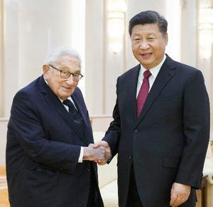 北京の人民大会堂でキッシンジャー元米国務長官(左)と握手する中国の習近平国家主席=8日(共同)