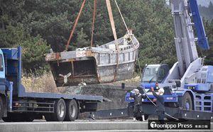 クレーンでつり上げられ撤去される木造船=深浦町の十二湖海浜公園