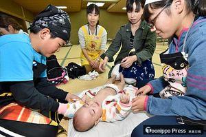 赤ちゃんに服を着せる板柳北小の児童たち