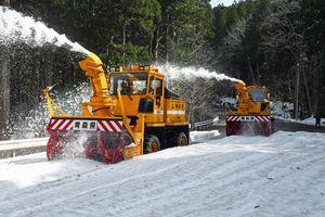 雪を飛ばしながら恐山街道を除雪するロータリー車