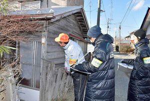 空き家とみられる建物を調べるヴァンラーレの山田賢二選手(右)と穂積選手(中央)