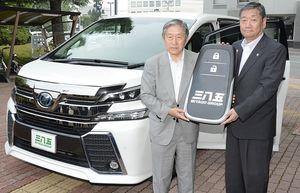 車両キーの目録を手にする泉山会長(左)と小林市長