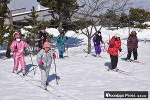 柴崎会長(後方左端)の指導を受けて、歩くスキーで汗を流す住民たち