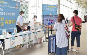 八戸駅に設けた検温コーナーで、新型コロナウイルスの感染予防を呼び掛ける八戸市職員ら=7日午前