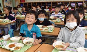 給食で出されたシジミ汁を手にする上北小学校の児童たち